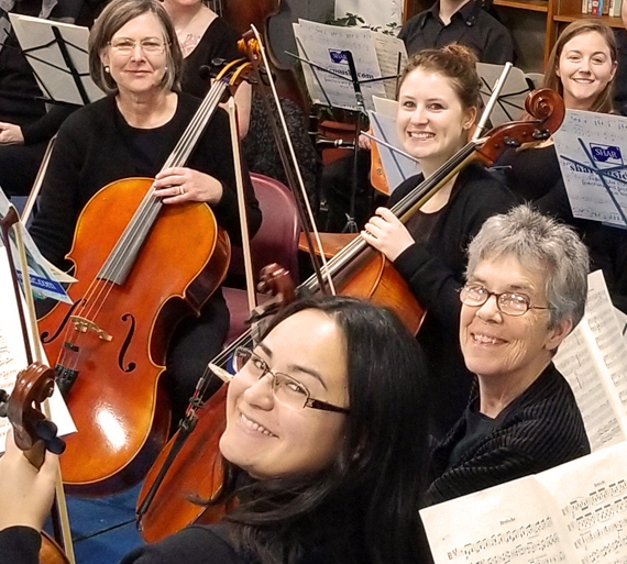Smiling cellists during a break in rehearsal
