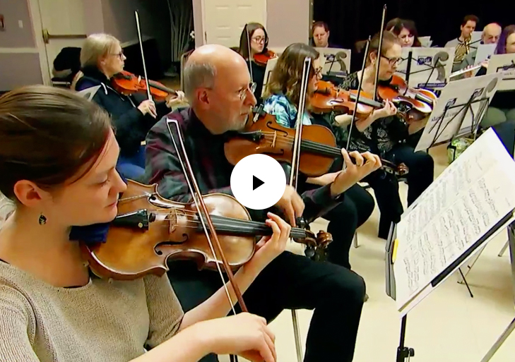 Violin section in rehearsal with play button